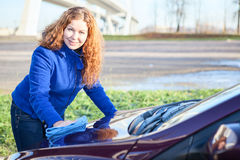 Woman polishing car cowl Royalty Free Stock Photography