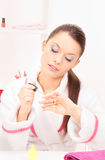 Woman polishing her nails Stock Photography