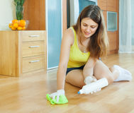 Woman  polishing parquet. With furniture polish at home Royalty Free Stock Photos