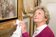 Woman polishing picture frames Stock Photos