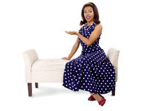 Woman in Polka Dot Dress Presenting Something. Young black female on a chaise lounge with advertising gesture Royalty Free Stock Photography