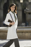 Woman in polo neck jumper and white coat walking in plaza, carrying handbag, smiling, portrait Royalty Free Stock Images