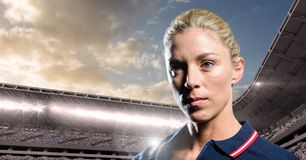 Woman in polo shirt in stadium with bright lights and sky with clouds Stock Photo
