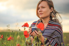 Woman in poncho with calabash on flower field Stock Photo