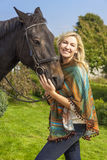 Woman in Poncho Leading Her Horse Stock Images