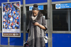 A woman in a poncho watching the phone is on the background of blue wall Royalty Free Stock Photo