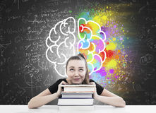 Woman with ponytail, books and brain sketch. Portrait of a girl with a ponytail sitting at her desk with her head resting on a stack of books. There is a brain stock photo