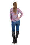 Woman With Ponytail Standing Rear View. Young woman in jeans, black boots and lumberjack shirt standing with hand on hip. Rear view. Full length studio shot Stock Photography