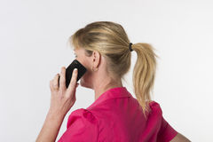 Woman with ponytail using a phone Stock Images