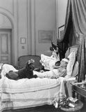 Woman and poodle sitting next to an injured man in bed Stock Photos