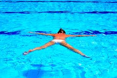 Woman in Pool. Woman Relaxing In Pool Laying On Water Surface Stock Photo