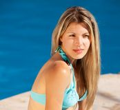 Woman by Pool. An attractive woman relaxing by an outdoor pool Stock Image