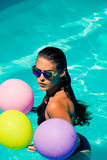 Woman in pool with balloons Stock Photography