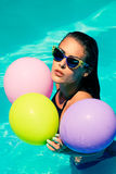 Woman in pool with balloons Royalty Free Stock Image