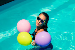 Woman in pool with balloons Stock Image