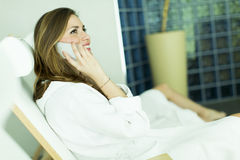 Woman by the pool. Woman in a bathrobe on the phone by the pool Stock Photography