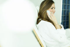 Woman by the pool. Woman in a bathrobe on the phone by the pool Royalty Free Stock Image