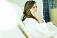 Woman by the pool. Woman in a bathrobe on the phone by the pool Royalty Free Stock Photos
