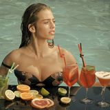 Woman in pool with cocktail and fruit at summer vacation. Near blue water Royalty Free Stock Photography