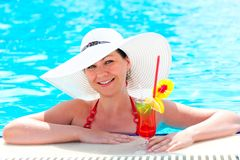 Woman in the pool with a cocktail in a hat Stock Photos
