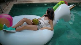 Woman in pool drinking a coconut fruit. Close-up of woman portrait smiling and drinking a long cocktail from coconut fruit on exotic island resort stock footage