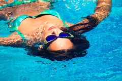 Woman in pool. Woman float at pool with sunglasses, summer day, shot from above, natural light, shallow depth of field Royalty Free Stock Photo