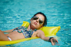 A woman in the pool floats on a blown mattress.  Royalty Free Stock Images