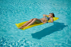 A woman in the pool floats on a blown mattress.  Stock Photography