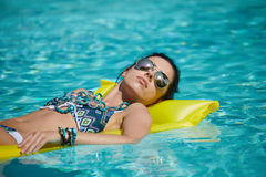 A woman in the pool floats on a blown mattress.  Royalty Free Stock Photo