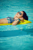 A woman in the pool floats on a blown mattress.  Royalty Free Stock Image