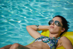 A woman in the pool floats on a blown mattress.  Stock Image