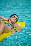 A woman in the pool floats on a blown mattress.  Stock Images