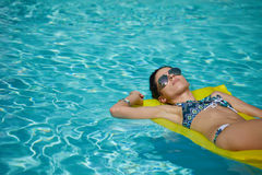 A woman in the pool floats on a blown mattress Royalty Free Stock Image