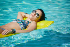 A woman in the pool floats on a blown mattress Royalty Free Stock Photography