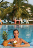 Woman in pool with fruits Stock Images