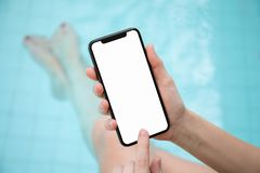 Woman in pool holding phone with an isolated screen stock photo