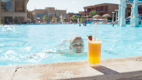 Woman in the pool with juice Stock Images