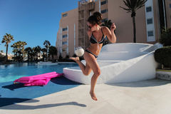 Woman beside pool kicking football Stock Photos