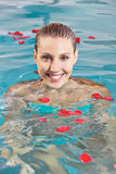 Woman in pool with leaves of roses Royalty Free Stock Photo