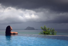 WOMAN IN POOL OVER OCEAN UNDER DARK STORM CLOUDS Stock Photo
