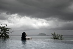 WOMAN IN POOL OVER OCEAN UNDER STORM CLOUDS Stock Photography