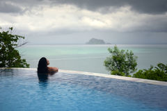 WOMAN IN POOL OVER OCEAN UNDER STORM CLOUDS Stock Images