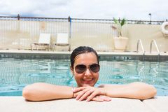 Woman at the pool's edge. Happy woman relaxing on the edge of an outdoor pool Royalty Free Stock Photo