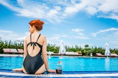 Woman in the pool with smoothie royalty free stock photography