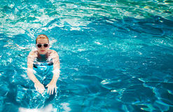 Woman in the pool. Vacation at caribbean resort. Young beautiful woman dives in swimming pool Royalty Free Stock Photo