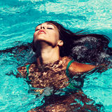 Woman in pool. Young attractive woman in  in pool with head thrown back Royalty Free Stock Photos