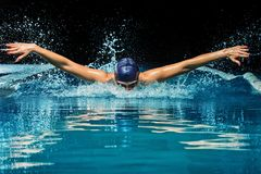 Woman in pool. Young woman in blue cap and swimming suit in pool Royalty Free Stock Photography