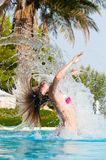 Woman at poolside. Slim woman is jumping and throwing wet hair back in swimming pool Royalty Free Stock Photography