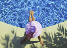 Woman poolside. Young woman in pink hat and bikini relaxing poolside Royalty Free Stock Images