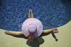 Woman poolside. Young woman in pink hat and bikini relaxing poolside Royalty Free Stock Image